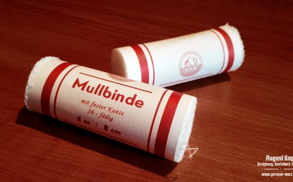 Simple medical bandage, rolled in paper wrapper with printed information: 4m length, 8cm width.
